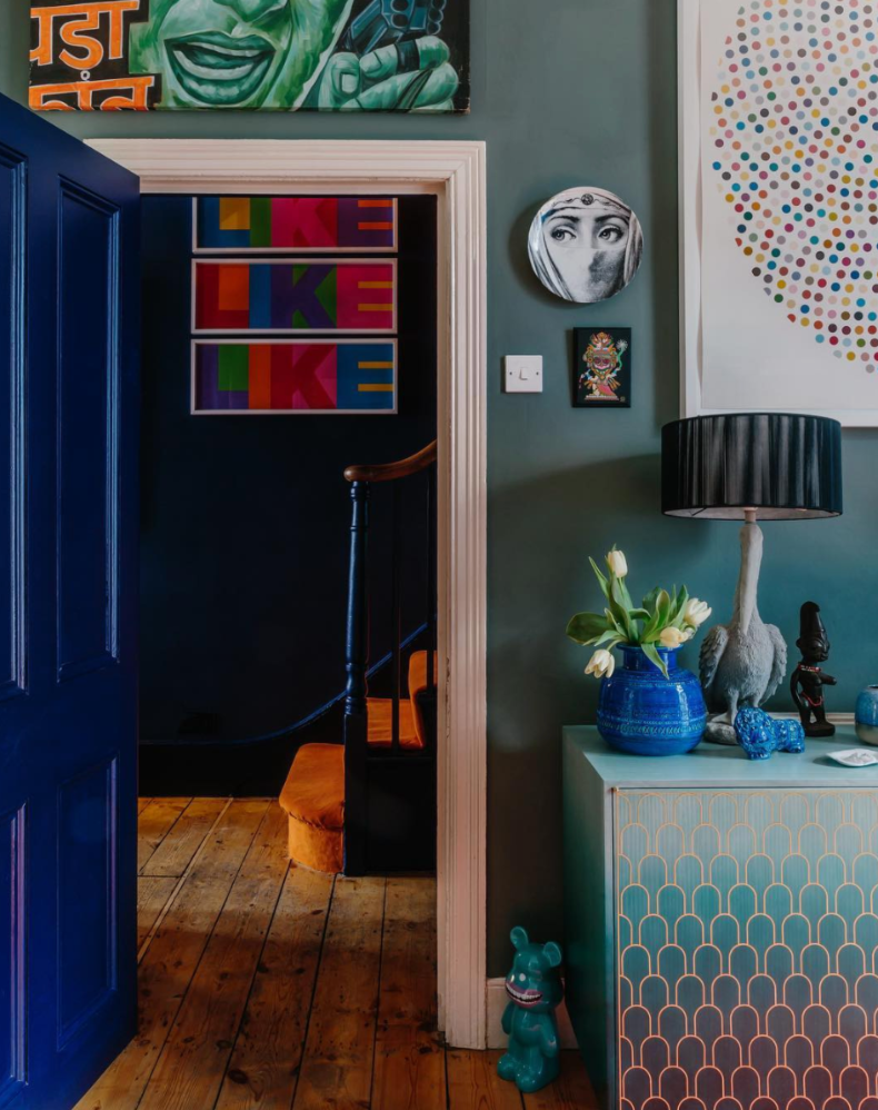 Maximalist home of Zoe Anderson, founder of W.A.Green. Dark hallway and living room with bright art and accessories.