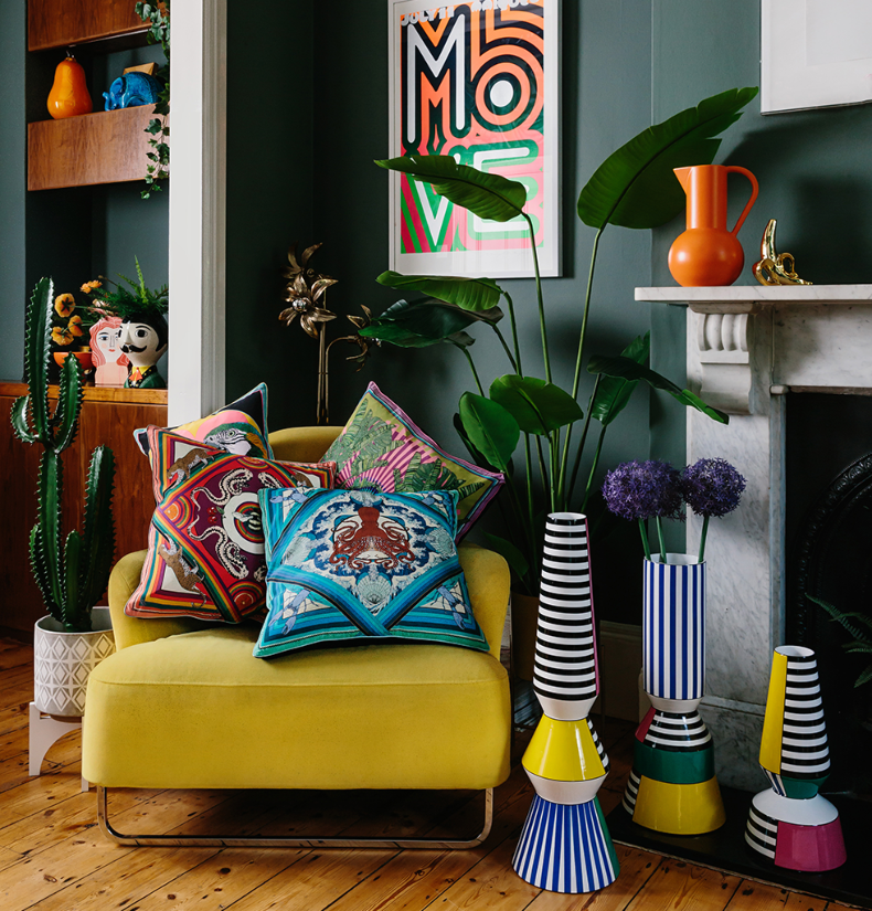 Quirky interiors by Zoe Anderson, wagreen.co.uk. Maximalist cushions, homeware and floor vases in colourful living room.